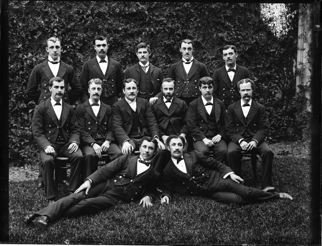 Group photograph of 13 young men in dark suits